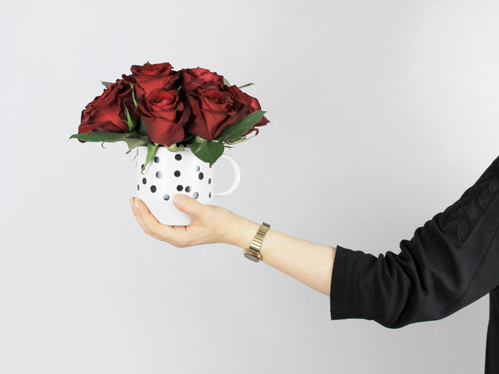 Blumendekoration für den Valentinstag: Rote Rosen in Tasse mit Punkten